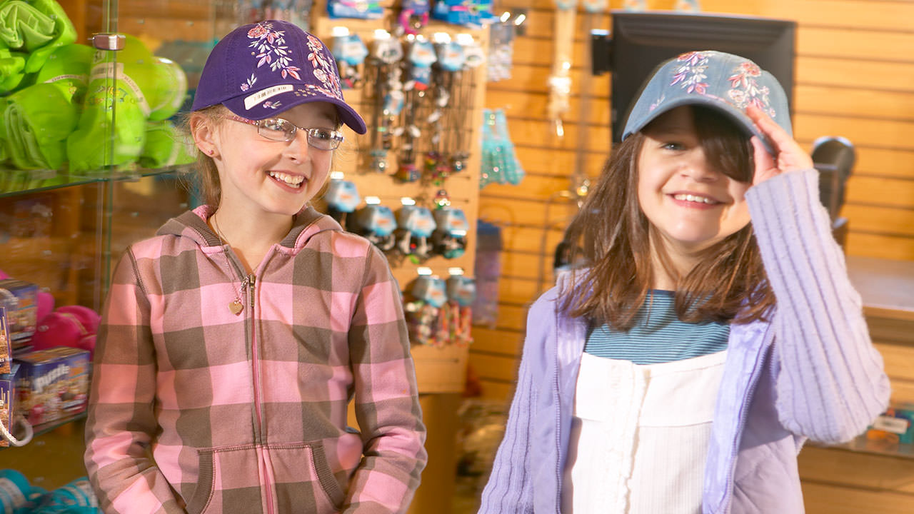Girls with hats on in gift shop